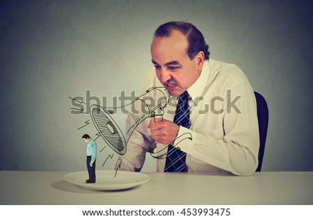 Business man boss screaming through megaphone at young scared colleague standing on a plate at his desk. Negative emotion bad business communication. Stressful job concept  - stock photo