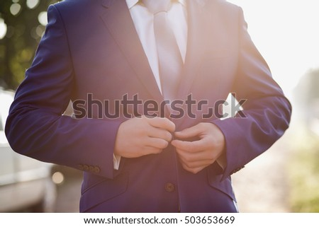 business man button his jacket on purple background.