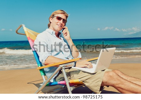 Business man calling by cell phone and working on computer at the beach