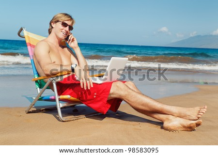 Business man calling by cell phone and working on computer at the beach in Hawaii - stock photo