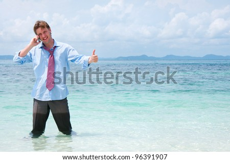 Business man calling by cell phone on the beach - stock photo