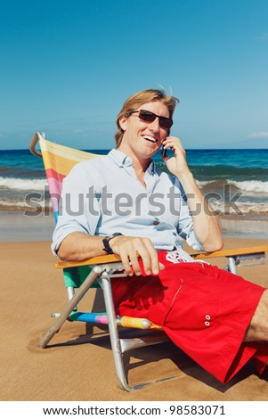 Business man calling by cell phone on the beach in Hawaii - stock photo