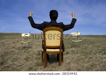Business man celebrate his success in front of two empty chair