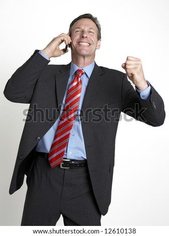 Business man celebrates deal whilst on the phone - stock photo