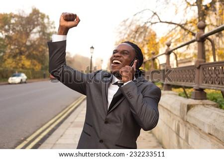 Business man celebrating on the phone. - stock photo