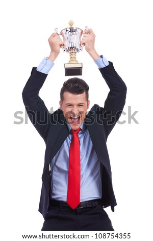 Business man celebrating with trophy over his head on white background - stock photo