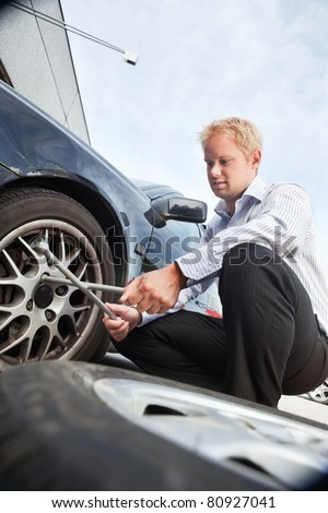 Business man changing a tire on the street - stock photo