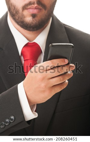Business man checking his smartphone while wearing a classic black suit and red necktie. - stock photo