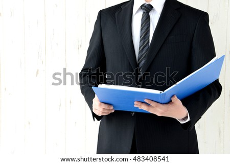 Business man checking material while thinking