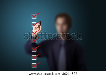 business man checking on checklist boxes - stock photo