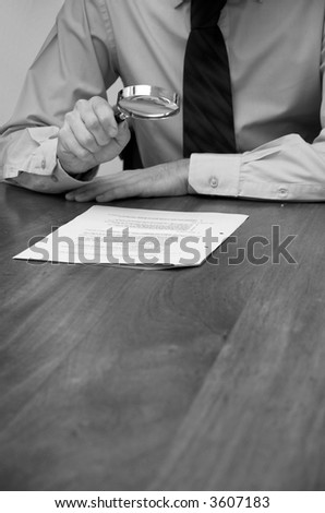 Business man checks the detail in a document with a magnifying glass.