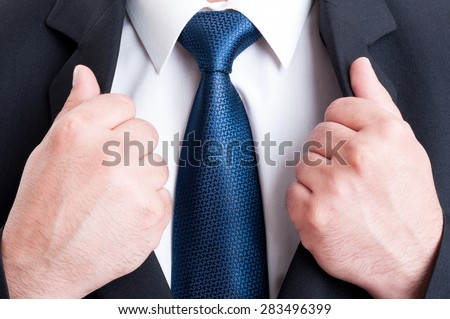 Business man chest as powerful leader concept. Black suit, white shirt and blue tie - stock photo