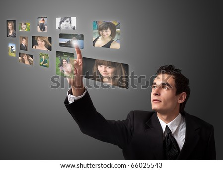 Business man choosing photos from digital gallery - stock photo