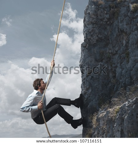 Business man climbs a mountain - stock photo
