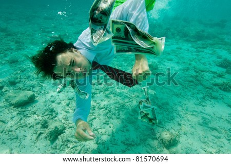 Business man collecting money swimming underwater, wearing formal clothes