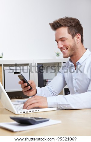 Business man connecting cell phone and computer wireless in office - stock photo