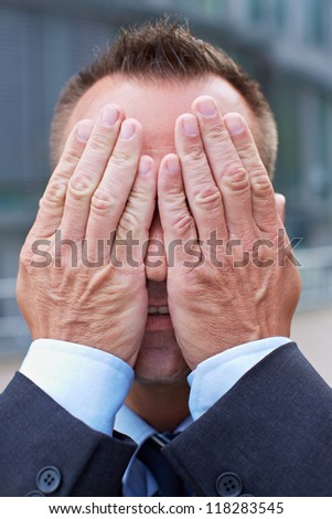 Business man covering his face with his both hands - stock photo