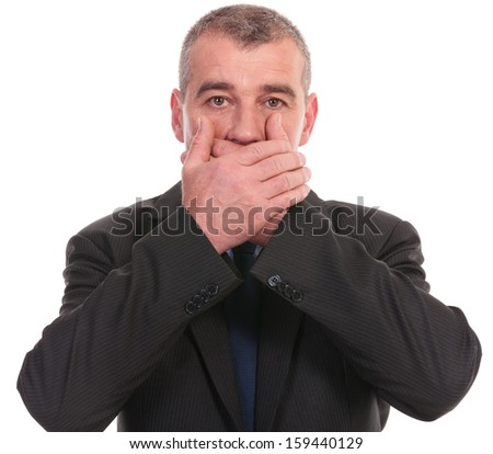 business man covering his mouth while looking into the camera. on a white background - stock photo