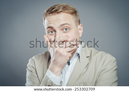 Business man covers his mouth with his hands, fear, does not want to roar, laughing - stock photo