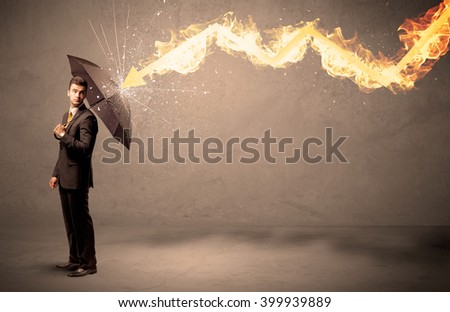 Business man defending himself from a fire arrow with an umbrella on grungy background - stock photo