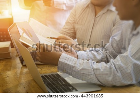 business man discussing market research with colleagues in a meeting. Team of young professionals having a meeting in conference room looking at documents.,vintage color,selective focus  - stock photo