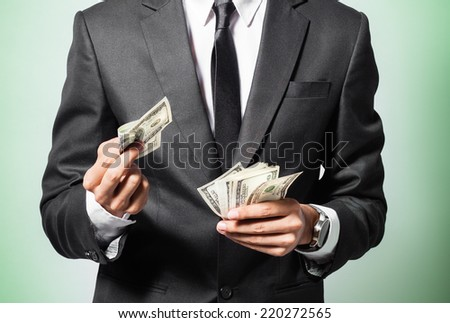 Business man displaying a spread of cash over a green background - stock photo