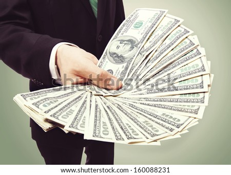 Business Man Displaying a Spread of Cash over Vintage Green Background  - stock photo