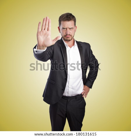 Business man doing stop sign over orange gradient background