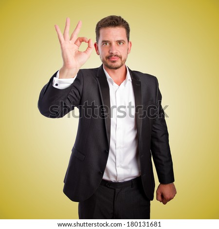 Business man doing the ok symbol over orange gradient