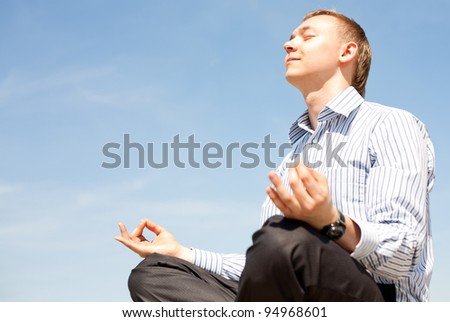 Business man doing yoga exercises outdoors and relaxing - stock photo