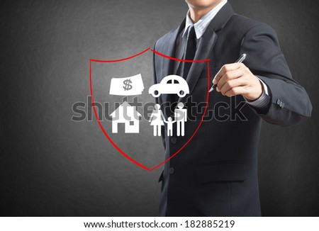 Business man drawing shield protecting family, house, car money.  insurance concept - stock photo