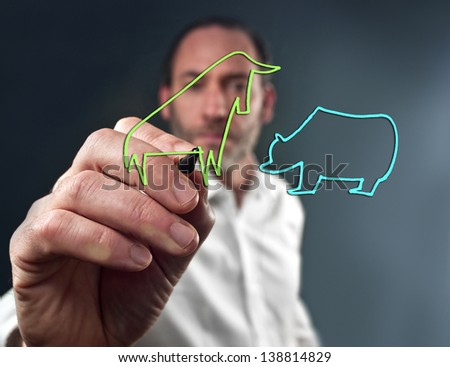 Business man draws the stock market bull and bear - stock photo