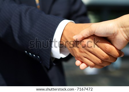 Business man dressed in suit shaking hands with another person. Concept: Deal done or agreement made. - stock photo