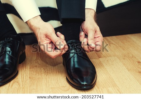 Business man dressing up with classic, elegant shoes. Groom wearing shoes on wedding day, tying the laces and preparing. Vintage effect