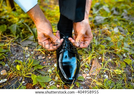 Business man dressing up with classic, elegant shoes. Groom wearing shoes on wedding day, tying the laces and preparing on the grass. - stock photo