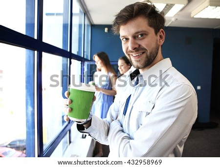 business man drinking coffee and looking and smiling at the camera, in modern office. - stock photo