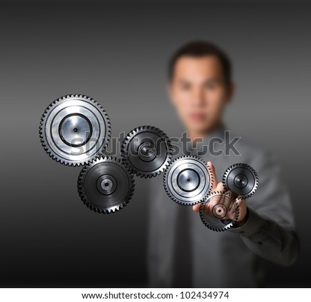 business man driving set of gears - concept of industry, machine, teamwork, power, and advance