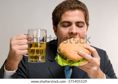 Business man eating a hamburger with a glass of beer