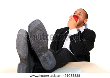 Business Man Eating An Apple A young satisfied businessman sitting by desk at office feet on table eating an apple. Isolated over white. - stock photo