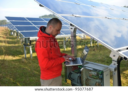 business man  engineer using laptop at solar panels plant eco energy field  in background - stock photo