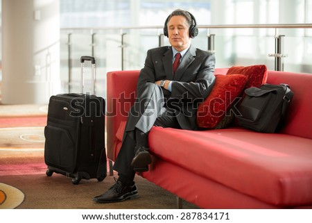 Business man executive relaxing at the airport listening to music on headphones - stock photo