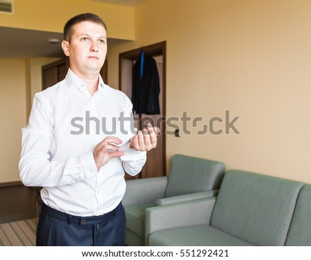 Business man fastening buttons on shirt sleeve at home