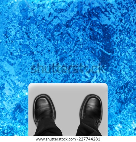 Business man feet on ledge of diving board, overhead view - stock photo