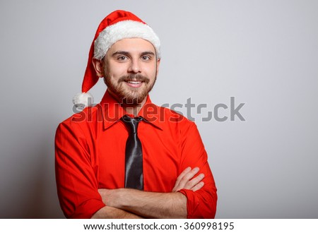 Business man folded his arms crosswise. Winter, corporate party, Christmas hat isolated portrait of a man on a gray background, studio photo.