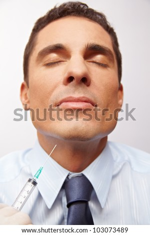 Business man getting needle in chin at cosmetic surgery - stock photo