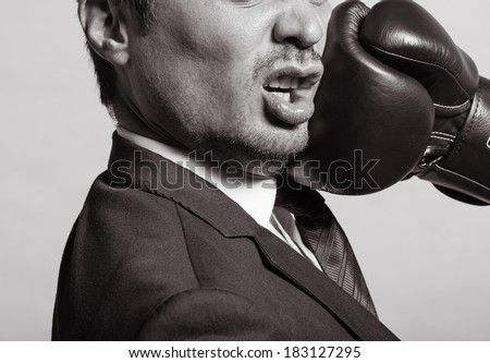 Business man getting punch with boxing glove. - stock photo