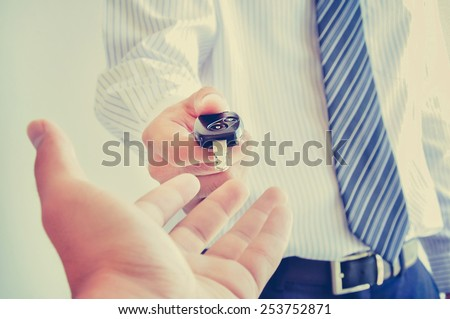 Business man giving a car key - vintage (retro) style color effect - stock photo