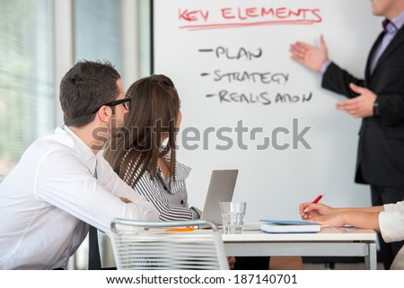 Business man giving a presentation to colleagues in office environment - stock photo
