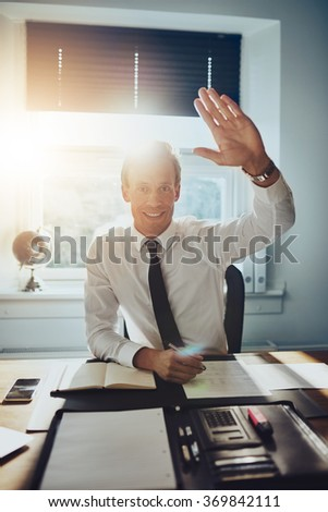 Business man giving high five to camera while smiling, wearing suit and tie - stock photo