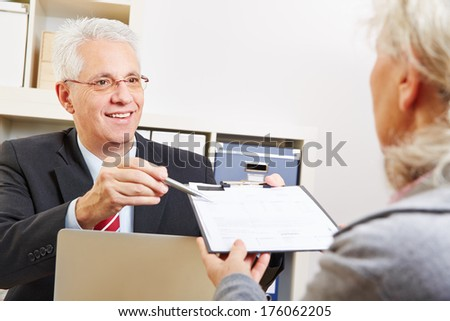Business man giving senior woman contract to sign on a clipboard - stock photo